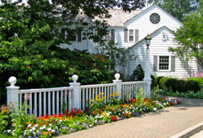 Decorative custom fence is included in this garden featuring a mix of perennial and annual flowers.